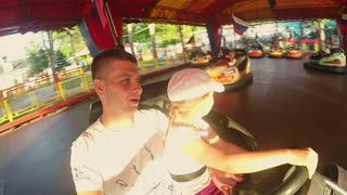 Father and daughter having fun on bumper car in amusement park. Overhead view of the driver, drive, fun, speed.