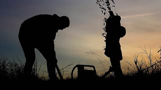 Father and daughter planting a tree. Sunset. Silhouette. Spring. The concept of family values.