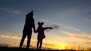 Father and little daughter silhouettes play at sunset. Concept of friendly family. Slow Motion.