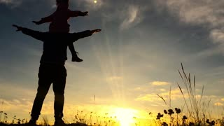 Father and little daughter silhouettes play at sunset. Father trowing happy child girl daughter air sunset landscape. Concept of friendly family. Slow Motion.