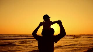 Father and little son walking and playing on the beach at sunset.