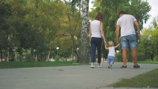 Father and Mother with son holding hand in the park. Family walk in the park.