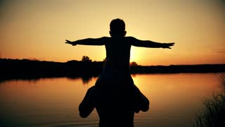 father and son silhouettes playing on beach boy rising up hands imitating a flight at wonderful sunset through the shining sun happy family concept of a united family