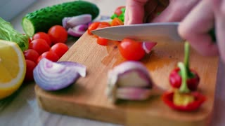 Female chef's hands cut, chop, red cherry tomatoes on wooden cutting board. Summer healthy vegan vegetables salad.