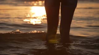 Female feet of hiker tourist walking barefoot on shore. Legs of young woman going along ocean beach. Girl stepping on wet sand of shoreline. Slow motion. Close up.
