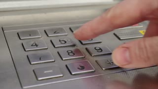 Female hand enter atm banking cash machine pin code. Woman pressing keypad of an ATM machine.