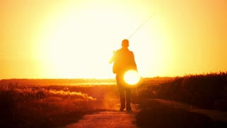 Fisherman walking at sunset sky background. The man is holding a fishing rod and tackle. Go off into the distance at sunset, concept, lifestyle.