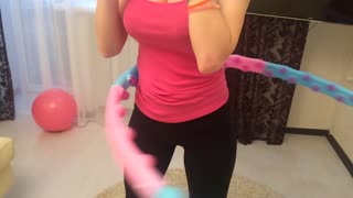 Fitness at home. Girl turns hula hoop on waist. Young woman doing stretching exercises at home.