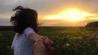 Follow me. Happy couple taking hands and having fun outdoors. Couple running away on the meadow. Countryside. Slow motion 120fps FHD 1080p