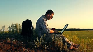 Freelancer working with laptop in a nature. Man working with laptop sitting on the rocky mountain on beautiful scenic background. Freelance concept.