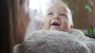 Funny cute baby sitting on the toy dog and smiling