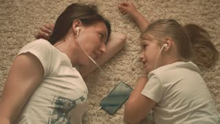 Funny footage of young woman with little daughter lying on the floor looking at each other and listening to music on the phone, they use one earphone.