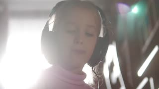 Funny little girl in headphones sitting in child room singing and music.