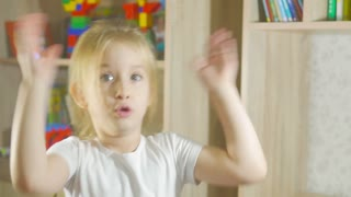 Funny little girl in singing standing in children's room, moving and laughing
