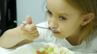 Funny little girl sitting at kitchen table and eating fruit salad from bowl.