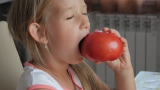 Funny little girl sitting at kitchen table and eating organic vegetables ripe red tomato.