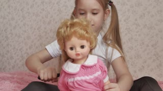 Girl combs doll hair by hairbrush