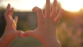 Girl doing heart hands against the sky, child hands forming a heart shape with sunset silhouette, love, dream, summer