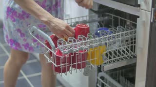 Girl emptying dishwasher. Girl Doing House Chores. Girl's hand picking plates from dishwasher. Female is working in domestic home kitchen.