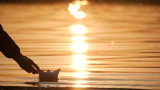 Girl hand launches paper boat on the water and pushing it away during beautiful sunset with reflection sun in the sea. Slow motion.