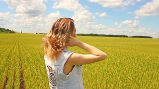 Girl in a blue dress goes on green field, hands touching ears, close-up.