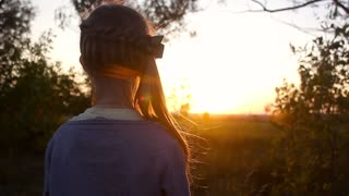 Girl in field of grass looking at the setting sun. Girl looking at the sunset on a meadow.