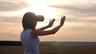 Girl in virtual reality goggles in field on sunset. Woman looking at virtual reality glasses at sun.