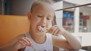Girl is sitting in a cafe and eating chicken. Concept fast food.
