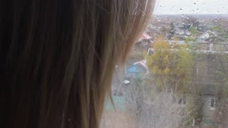 Girl looking out of window a rainy day