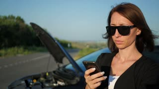 Girl near broken car on road is calling on mobile phone.
