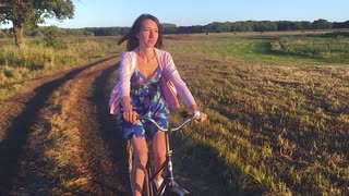 Girl on a bicycle in a field. Slow Motion.