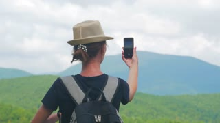 Girl on mountain top, female tourist taking photo of on cell smart phone. Young woman traveler on a background of mountains takes photos on a mobile phone.