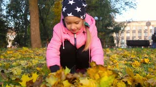 Girl play in autumn park. Children throwing yellow and red leaves.Baby with oak and maple leaf. Fall foliage. Family outdoor fun in autumn. Toddler kid or preschooler child in fall