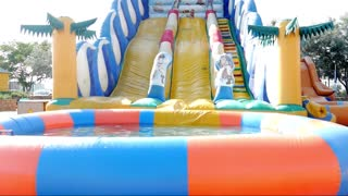 Girl sliding down on water slide in waterpark.