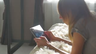 Girl using digital tablet computer and laying on bed.