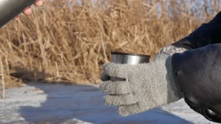 girl with thermos and cup hot tea in frosty day