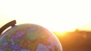 Globe at sunset in the field. Travel and global issues concept.