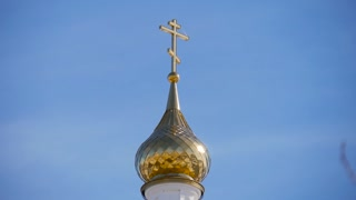 Golden dome of the Orthodox church in Central Russia on the blue sky background.