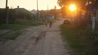 Group of happy children playing outdoors in village and running towards camera, all wearing similar knit clothes on warm summer day at sunset.