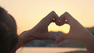 Hands forming a heart shape with sunset silhouette. Ocean sun shining through heart shaped female hands. Love. Nature. Hope. Freedom.