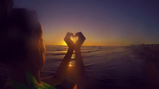 hands forming a heart shape with sunset silhouette