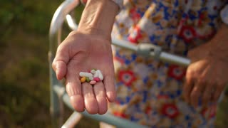 Hands of very old woman taking pills, close up of an elderly woman hand her medication, health issues at an old age, taking several medicines.