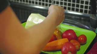 Hands of woman washing vegetables at her kitchen.