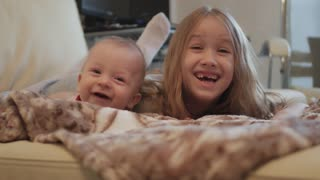 Happy baby boy and preschool girl lying on sofa, cheerful smiling children brother sister having fun together playing at home, friendship between siblings concept.
