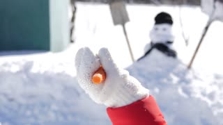 Happy baby girl builds a snowman, make a nose out of fresh carrots. Concept of: winter holidays, game, christmas.