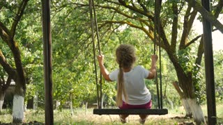 Happy cute little child girl have fun sway spin on a swing on nature.