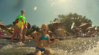 Happy family lifestyle. Baby girl splashing and jumping with fun in breaking waves. Summer travel, water sport outdoor activities, swimming lessons on tropical beach holiday with kids.