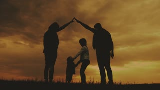 Happy family making the home sign at the sunset time. Happy parents making home for kids in beautiful nature. Concept of friendly family.