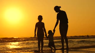 Happy family mother with two children on vacation at the beach. Silhouette mother with two children in the sea at sunset.