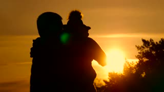 Happy family: silhouettes father and son baby playing at sunset.
